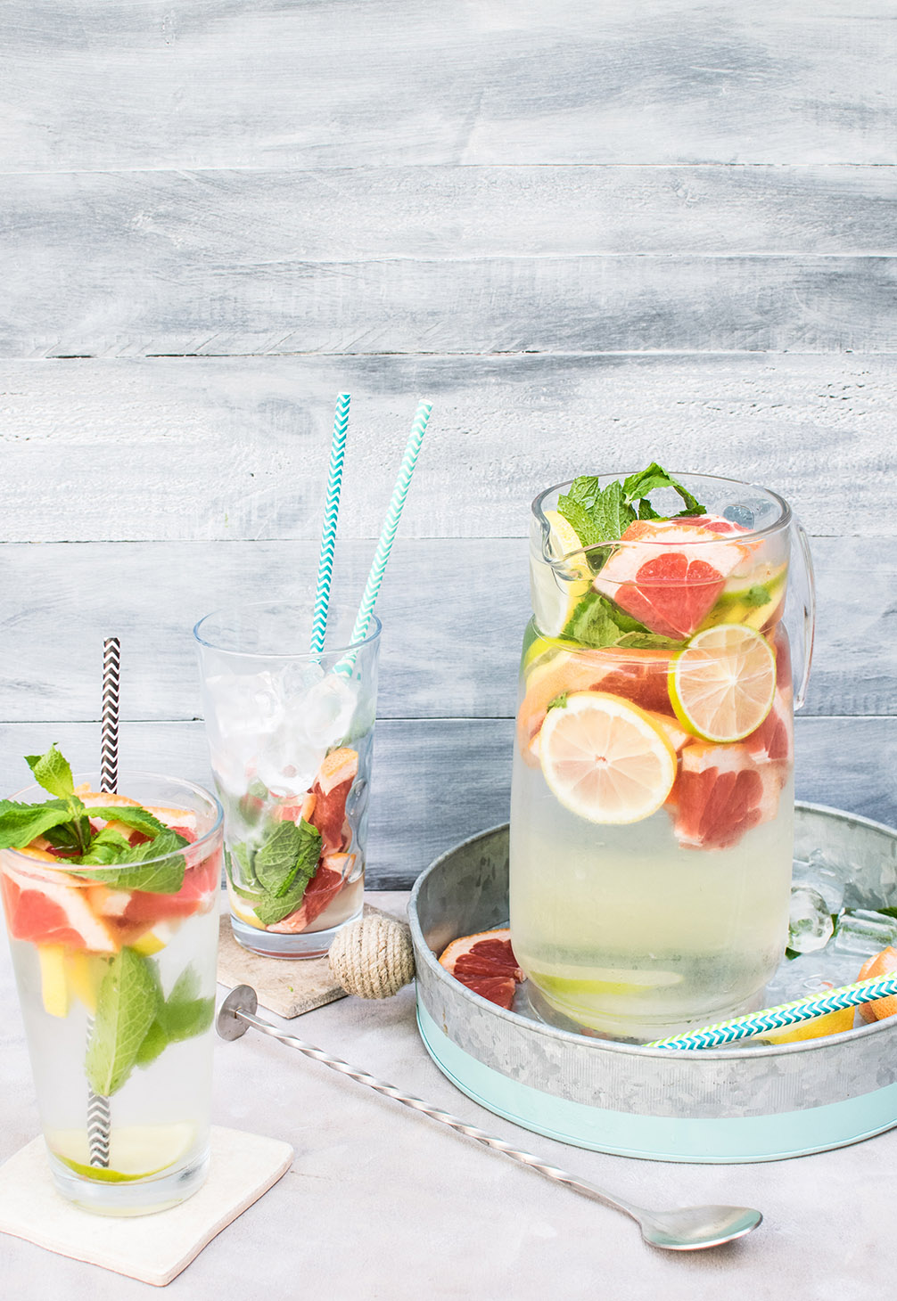 pitcher of water with cut lemons, grapefruit and mint